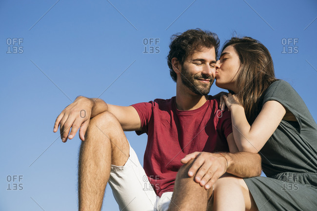 Young woman kissing man while sitting against clear sky