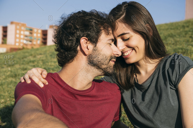 Man and woman sitting face to face on grass