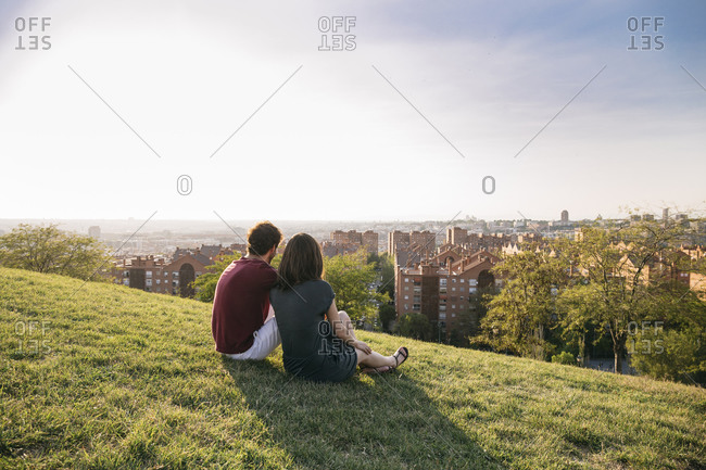 Couple admiring sunset view of city while sitting on grass