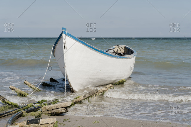 Boat moored at sandy coastal beach