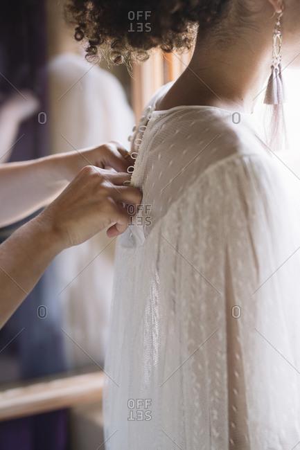 Woman hand closing wedding dress of bride at dressing room