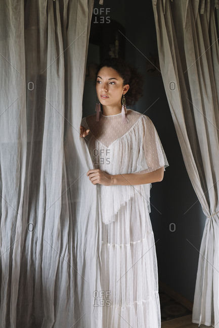 Young bride standing by curtain at dressing room