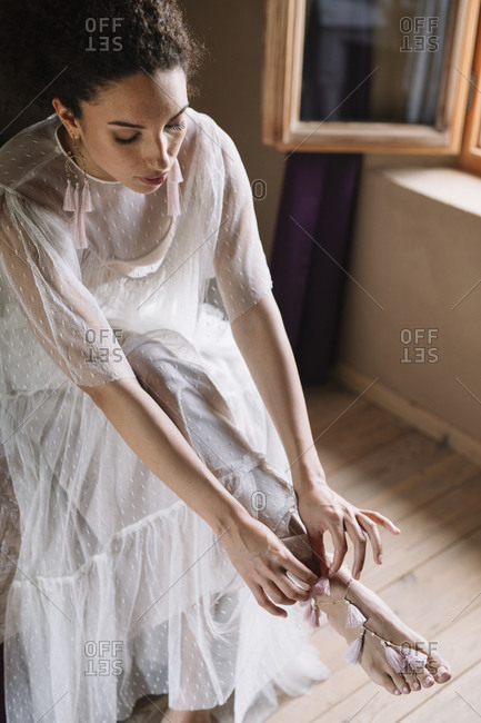 Bride wearing jewelry on leg while sitting by window at dressing room