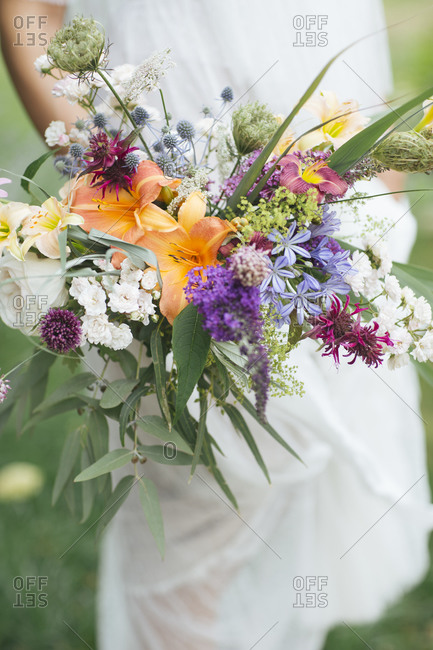 Bride hand holding bouquet while standing at garden