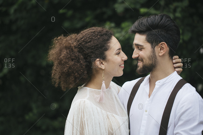 Lovely couple looking at each other while standing at garden