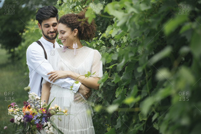 Groom embracing bride while standing at garden