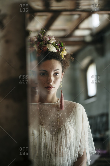 Bride with floral headband looking her reflection in mirror at dressing room