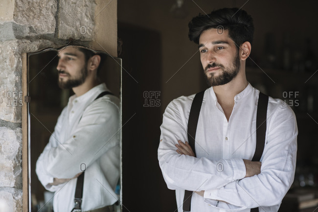 Groom standing with arms crossed at dressing room