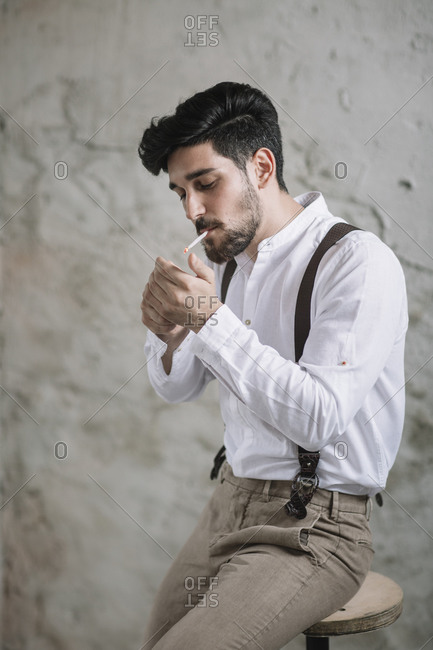 Young man igniting cigarette while sitting on table against wall