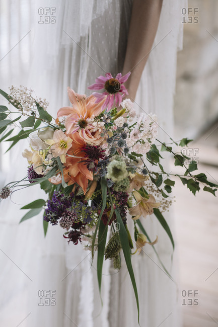 Bride standing while holding bouquet in hand