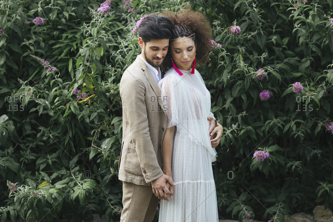 Loving couple embracing while standing against flowering plant