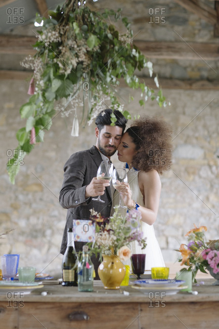 Couple toasting champagne flute while embracing at table