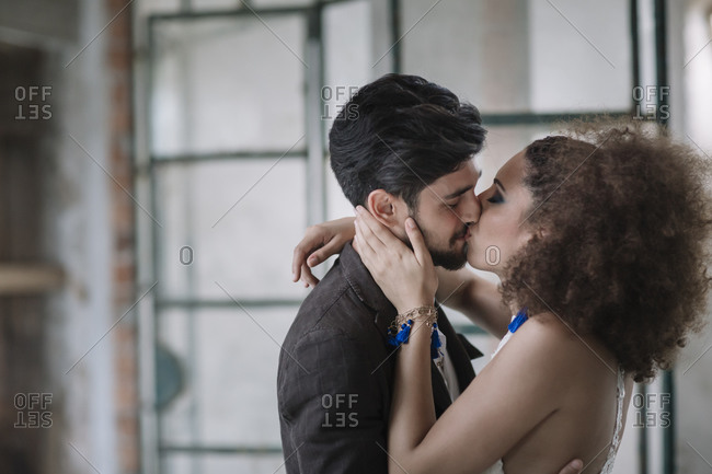 Just married couple kissing each other while standing at room