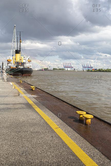 Germany- Hamburg- Cloudy sky over ship moored in Port of Hamburg