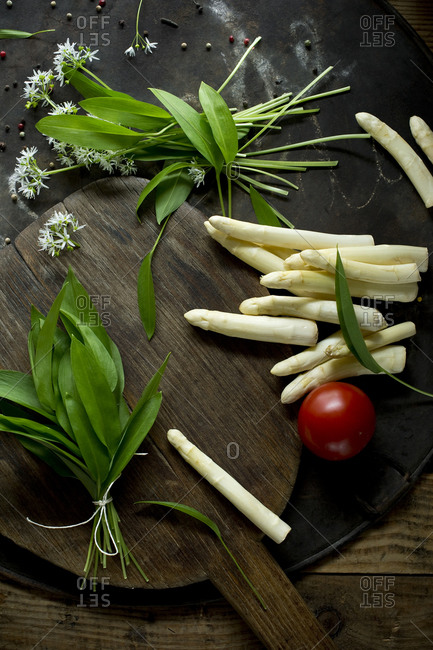 Peeled asparagus- bundled ramson- tomato and cutting board on rustic baking sheet