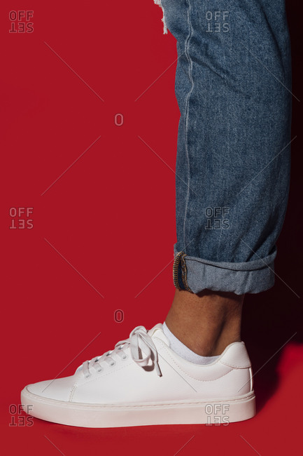 Feet of woman wearing sneakers while standing against red background