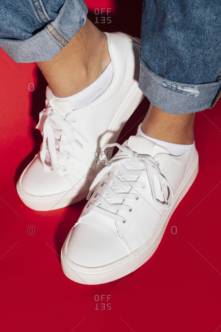 Close-up of female wearing sneakers on red background