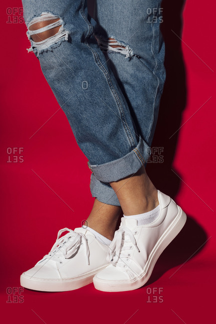 Close-up of woman wearing white sneakers with legs crossed standing against red background