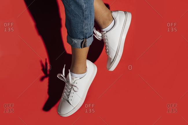Close-up of female wearing sneakers while jumping against red background