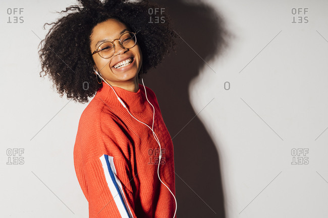 Smiling young woman listening to music against white background