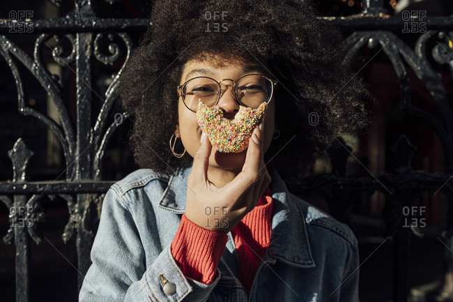 Close-up of young woman with curly hair eating donut against fence in city