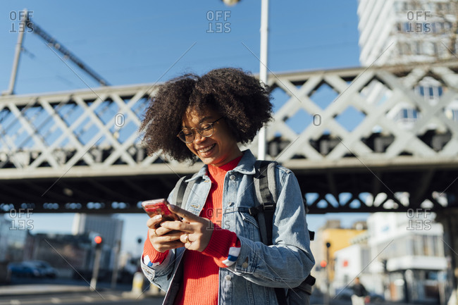 Smiling afro young woman using smart phone while standing against bridge in city