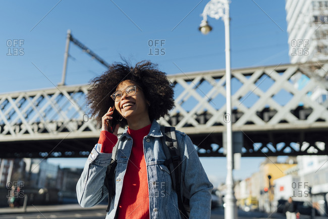 Cheerful afro young woman talking over smart phone while standing against bridge in city
