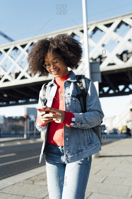 Afro young woman using smart phone while standing on sidewalk against bridge in city