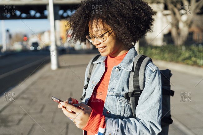 Close-up of smiling young woman with curly hair using mobile phone while standing on sidewalk