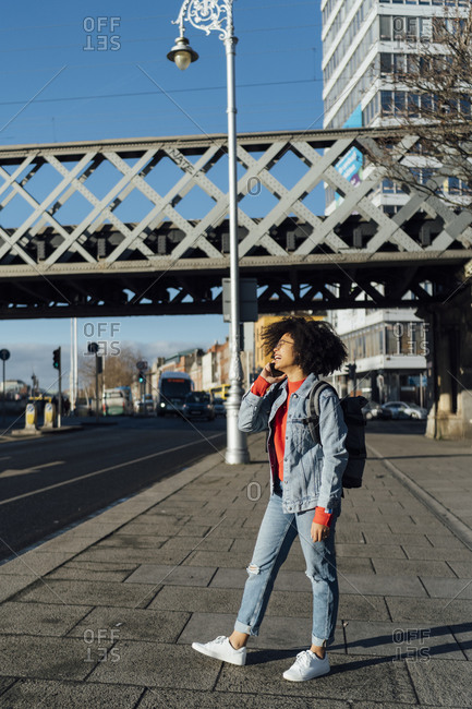 Afro woman talking over mobile phone while standing on sidewalk in city