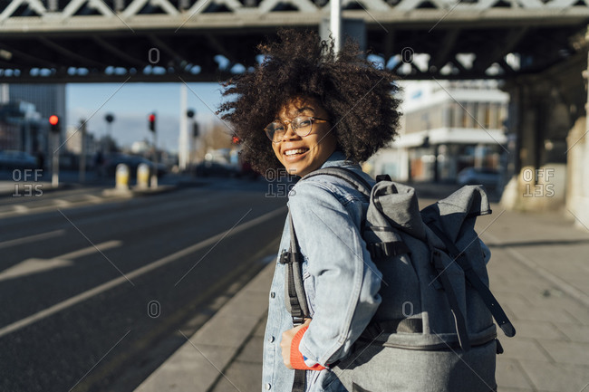 Smiling afro woman with backpack standing on sidewalk in city during sunny day