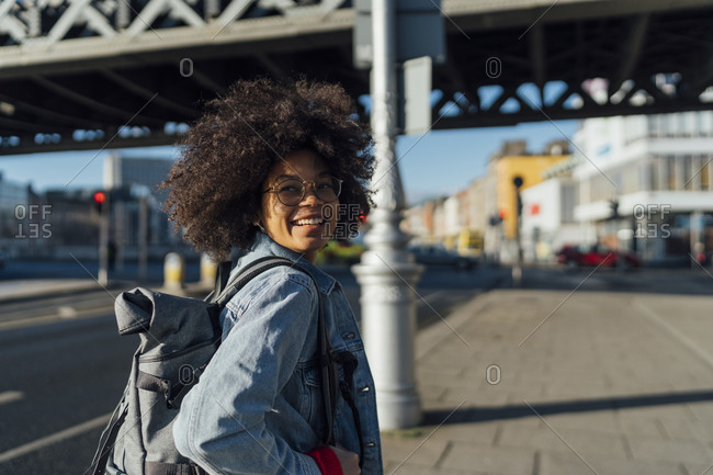 Smiling young woman with afro hair looking away while standing on sidewalk during sunny day