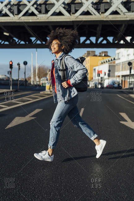 Cheerful young woman with afro hair running on street in city during sunny day