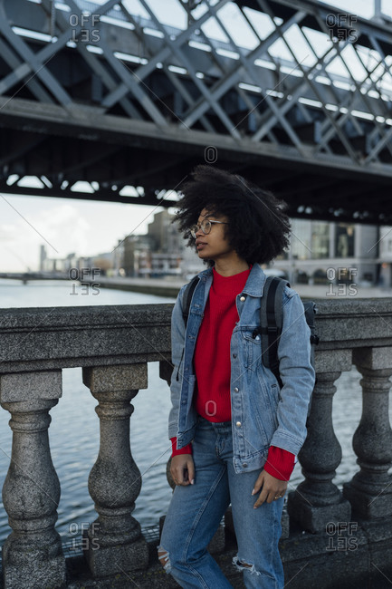 Thoughtful young woman with afro hair standing on footbridge over river in city