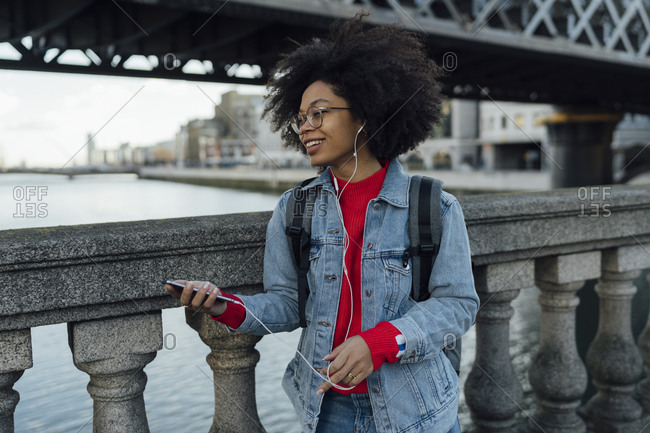 Afro young woman listening music through headphones while standing by railing on footbridge