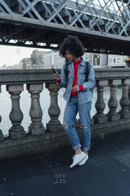 Afro young woman using mobile phone while standing on bridge in city