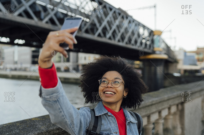 Smiling afro woman taking selfie with smart phone by railing in city