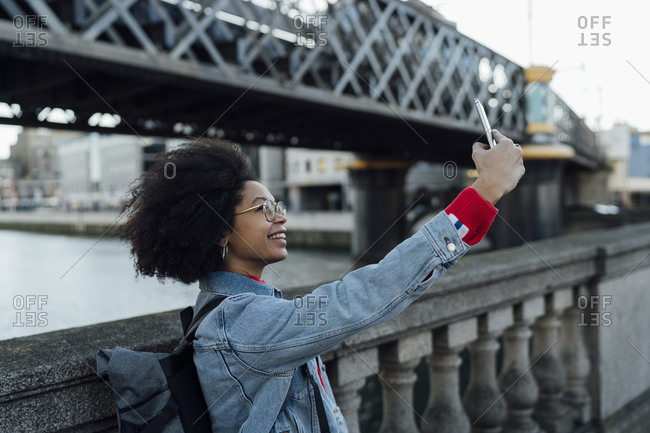 Afro young woman taking selfie with smart phone while standing by railing in city