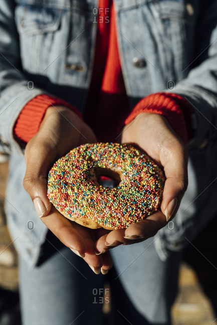 Close-up of young woman wearing denim jacket holding donut