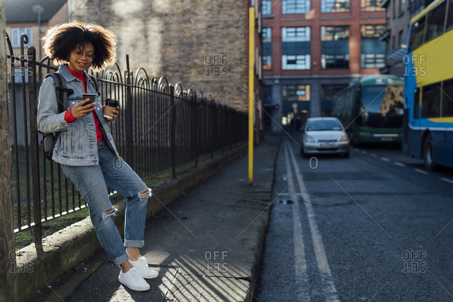 Afro young woman holding coffee cup using mobile phone while standing on street