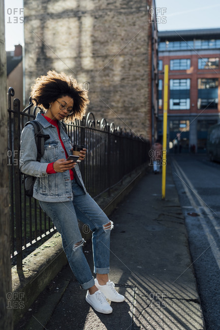 Afro young woman using mobile phone while standing by railing on street in city