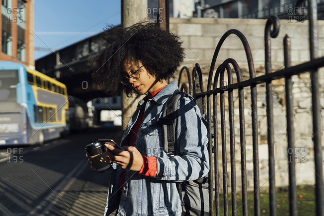 Young woman with curly hair using smart phone while standing by railing in city