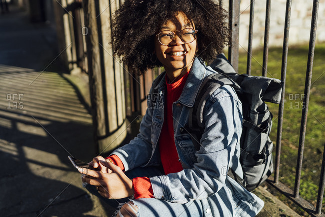 Smiling young woman with afro hair using smart phone while sitting by railing