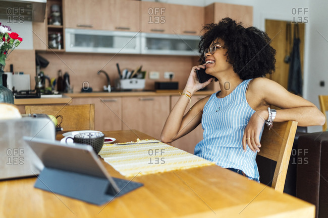 Cheerful young woman talking over smart phone while working in home office