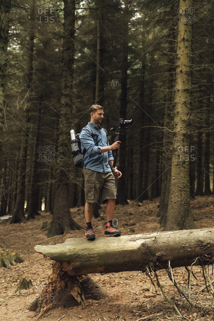 Man filming with camera and gimbal while standing on log against trees in forest