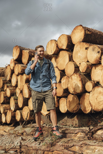 Mid adult man talking over smart phone while standing by woodpile in forest