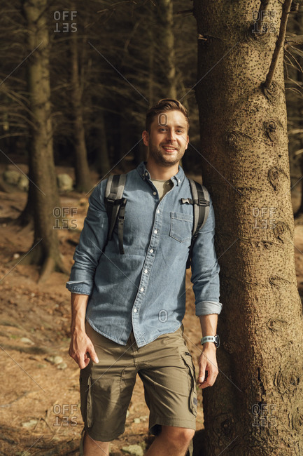 Handsome hiker standing by tree trunk in woodland