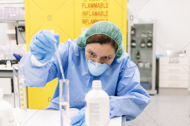 Female pharmacist mixing chemicals in graduated cylinder at laboratory