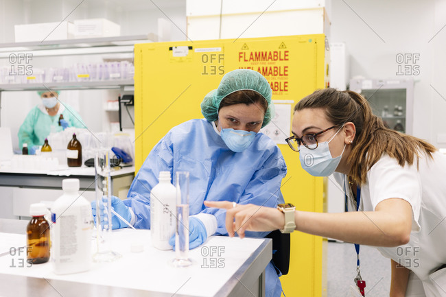 Female pharmacists discussing while preparing medicines in laboratory