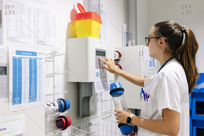 Female doctor using pneumatic tube system while standing in hospital
